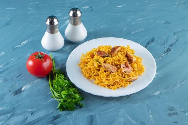 Macarrão com carne num prato ao lado de molho de salsa, tomate e sal, no fundo de mármore.