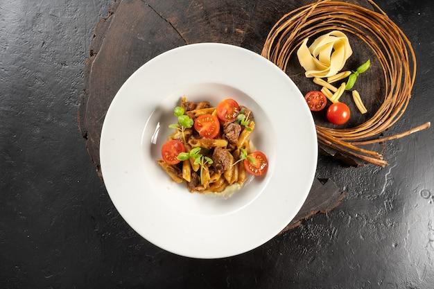 Macarrão com carne. penne, costela de boi, aipo, tomate cereja e queijo grana padano. um prato principal quente