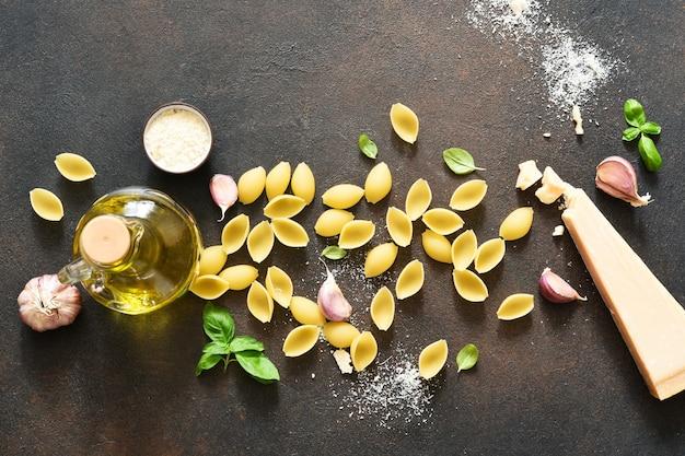 Macarrão com casca crua com parmesão, azeite e manjericão em um fundo de concreto. vista de cima. ingredientes para fazer macarrão.