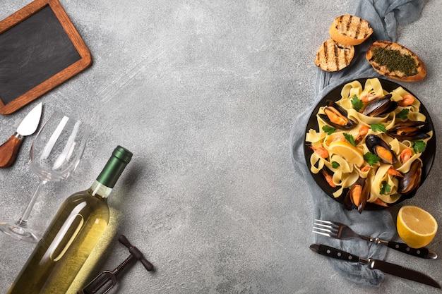 Macarrão com frutos do mar e vinho branco na mesa de pedra. mexilhões e camarões. vista do topo.