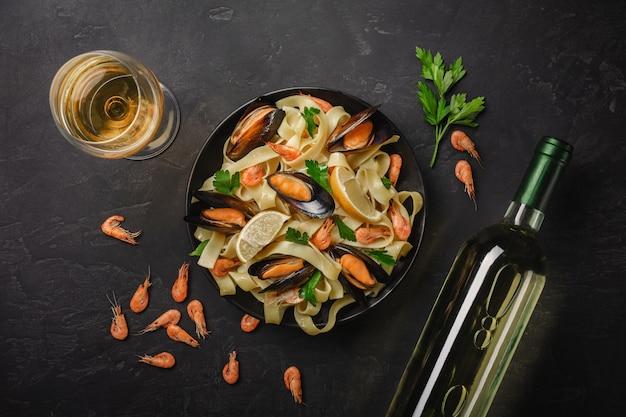 Macarrão com frutos do mar e vinho branco na mesa de pedra. mexilhões e camarões vista do topo.