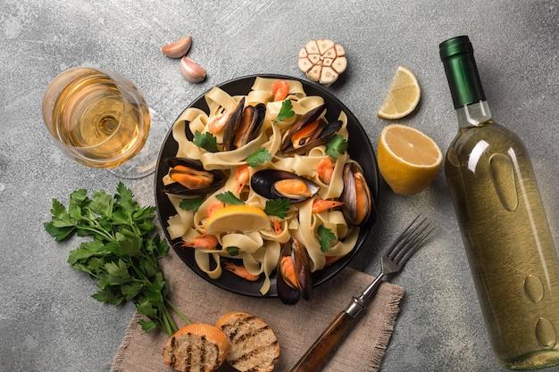 Macarrão com frutos do mar e vinho branco na mesa de pedra. mexilhões e camarões