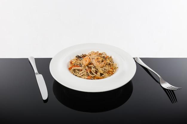 Macarrão com frutos do mar em uma mesa preta com um branco
