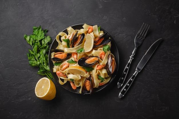 Macarrão com frutos do mar na mesa de pedra. mexilhões e camarões vista superior com espaço de cópia.