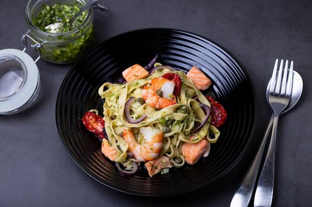 Macarrão com frutos do mar, tomates secos, alcaparras e cebolas roxas. massa caseira com camarão, salmão (truta) e molho pesto. fundo preto, placa preta. fechar-se.