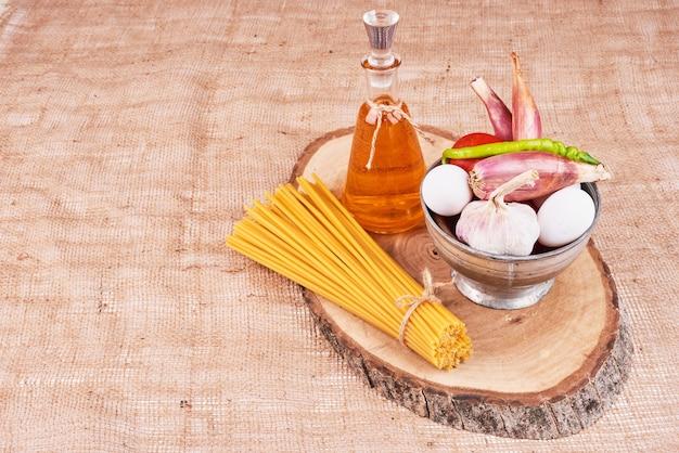 Macarrão com ingredientes em uma placa de madeira.