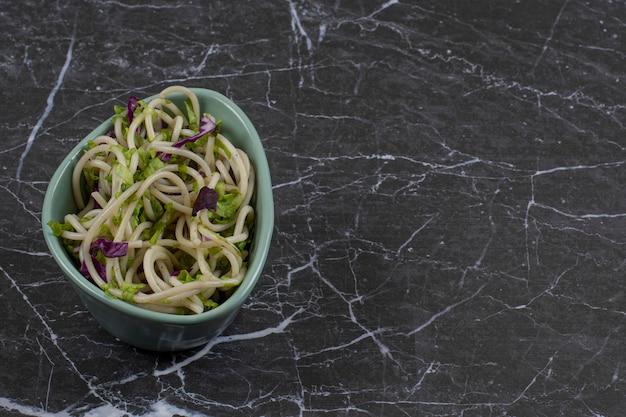 Macarrão com legumes e molho em uma tigela.