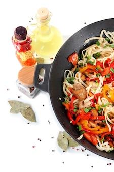 Macarrão com legumes na wok isolado no branco