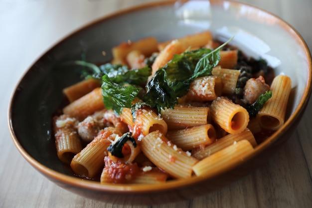 Macarrão com linguiça em molho de tomate na madeira, comida italiana