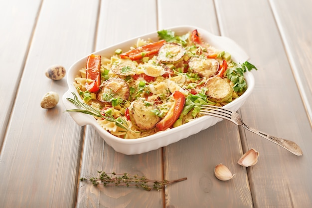 Macarrão com macarrão arcos e legumes, assados no forno.