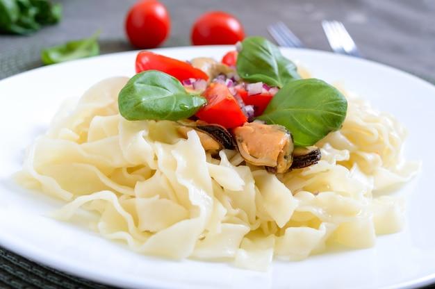 Macarrão com mexilhões, tomates em um prato branco sobre uma mesa de madeira. fechar-se