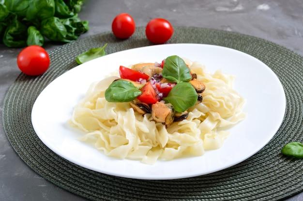 Macarrão com mexilhões, tomates em um prato branco sobre uma mesa de madeira