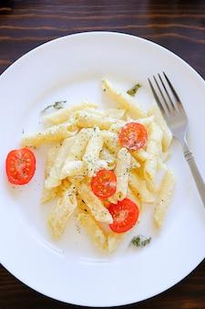 Macarrão com molho de creme, queijo, creme de leite, tomate, ervas e especiarias num prato branco sobre uma mesa de madeira.