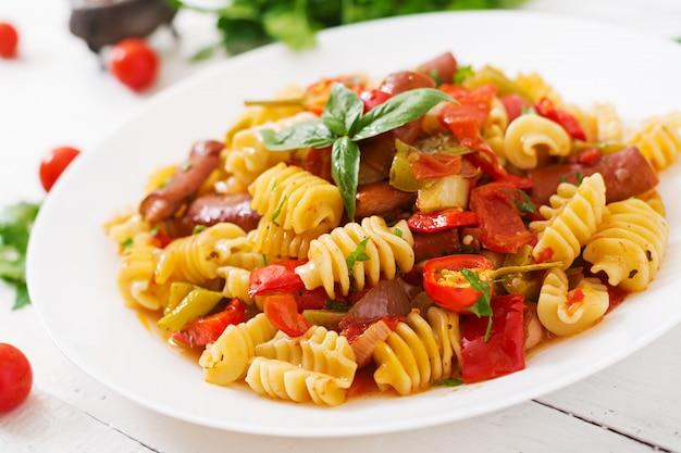 Macarrão com molho de tomate com salsicha, tomate, manjericão verde decorado em chapa branca sobre uma mesa de madeira.