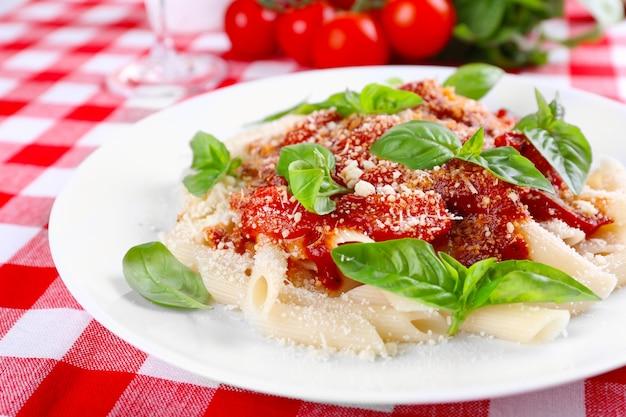 Macarrão com molho de tomate e manjericão na mesa close up