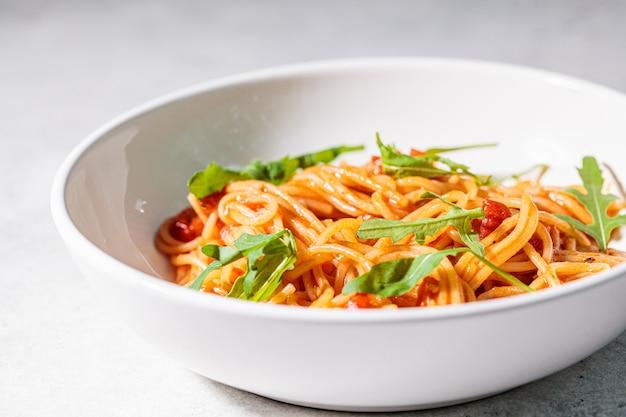Macarrão com molho de tomate e rúcula em uma tigela grande e branca. conceito de cozinha tradicional italiana.