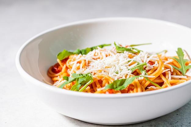 Macarrão com molho de tomate, queijo e rúcula em uma tigela grande e branca. conceito de cozinha tradicional italiana.