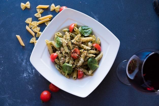 Macarrão com molho pesto, manjericão fresco e nozes no prato branco sobre fundo azul escuro