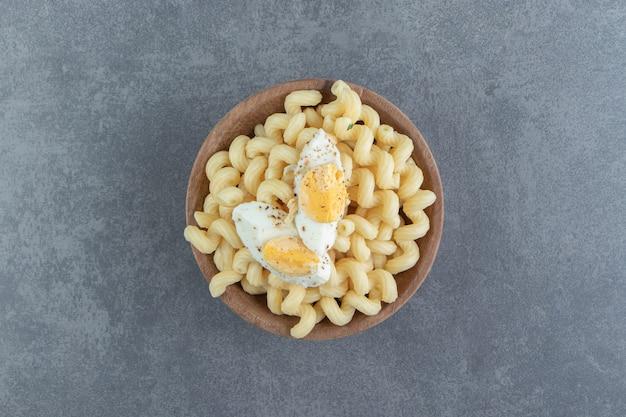 Macarrão com ovos cozidos em tigela de madeira.