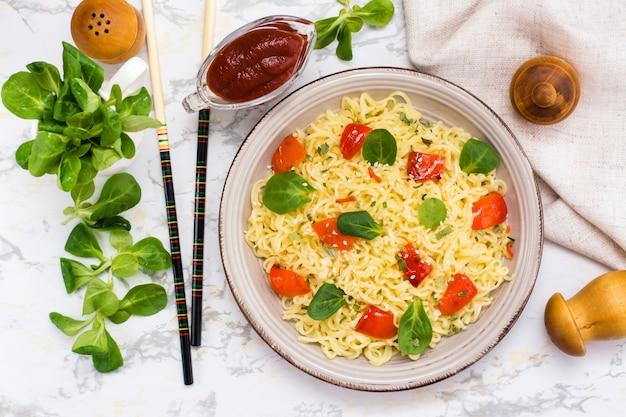 Macarrão com pimenta, folhas de alface e sementes de gergelim em um prato de cerâmica, vista superior