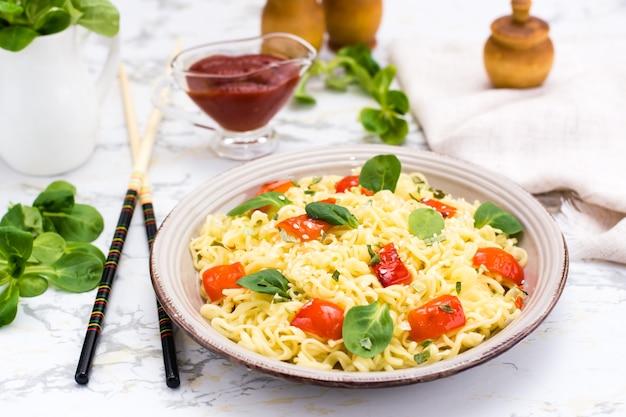 Macarrão com pimenta, folhas de alface e sementes de gergelim em um prato de cerâmica
