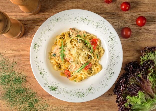 Macarrão com queijo e tomate em um molho branco com ervas e tomate cereja em um prato branco sobre uma mesa de madeira.