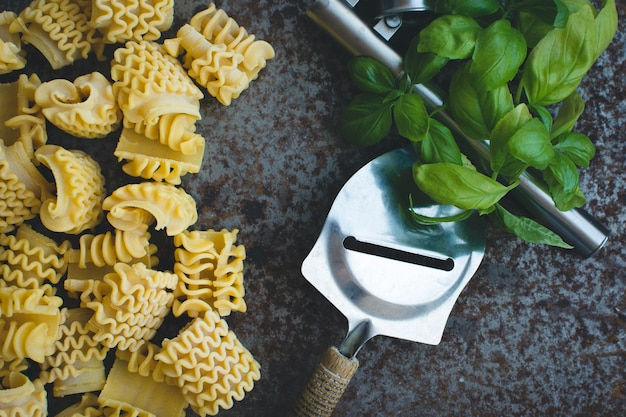 Macarrão com ralador de queijo e manjericão em um fundo metálico enferrujado