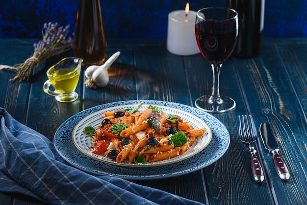 Macarrão com tomate cereja, azeitonas mussarela e espinafre, vinho e azeite em uma mesa de madeira. estilo rústico.