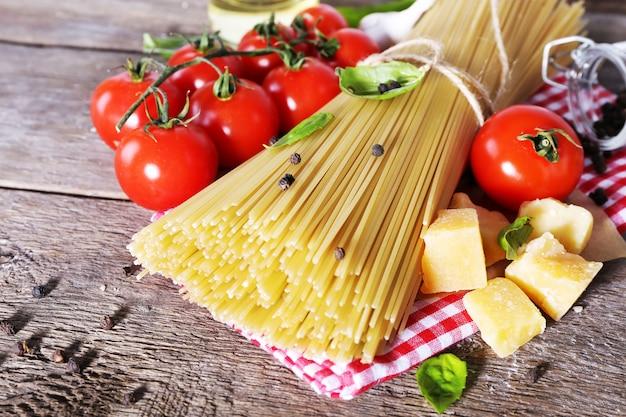Macarrão com tomate cereja e outros ingredientes na mesa de madeira