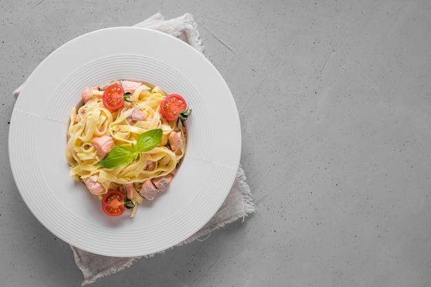 Macarrão com truta e tomate em chapa branca na luz. delicioso almoço mediterrâneo.