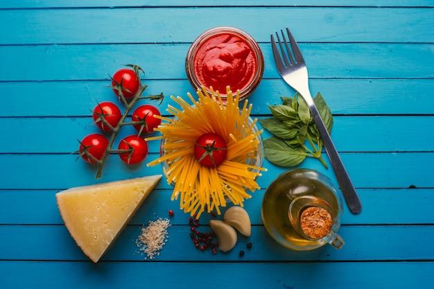 Macarrão com vários ingredientes para cozinhar comida italiana, em mesa azul