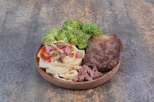 Macarrão com verduras e extrato de tomate, carne no prato branco
