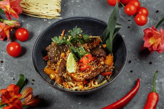 Macarrão com vitela e legumes em uma mesa cinza.