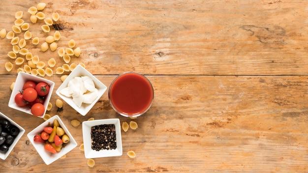 Macarrão conchiclioni cru; tigelas de tomate cereja; queijo mussarela; pimenta; azeitonas pretas; pimenta preta e molho sobre a mesa de madeira