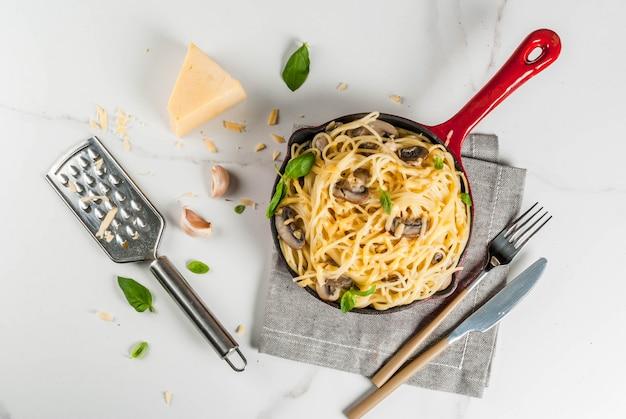 Macarrão cremoso de cogumelos com queijo e manjericão, em frigideira porcionada, na vista superior de mesa de mármore branco