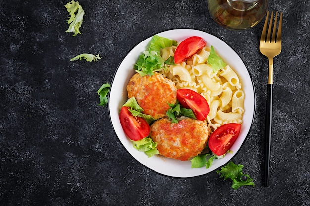 Macarrão creste e almôndegas de frango ao molho de tomate. vista superior, acima, copie o espaço