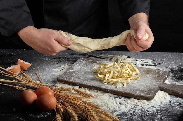 Macarrão cru caseiro feito de farinha, ovo na tigela de madeira no preto Foto Premium