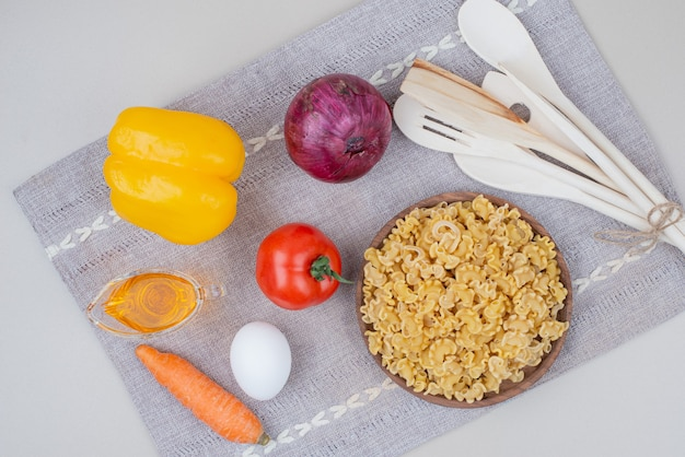 Macarrão cru com legumes em um prato de madeira na toalha de mesa
