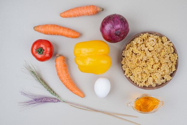 Macarrão cru com legumes no prato de madeira