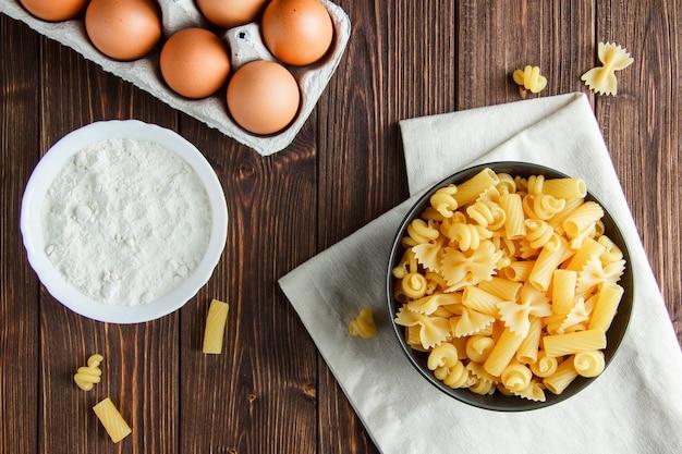 Macarrão cru com ovos, farinha em uma tigela de madeira e toalha de cozinha, plana leigos.