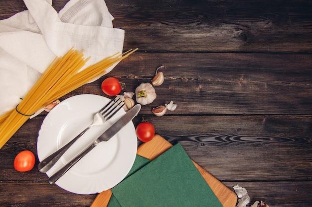 Macarrão cru com tomate na mesa