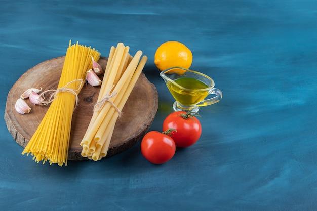 Macarrão cru com tomates vermelhos frescos e óleo em um fundo azul escuro.