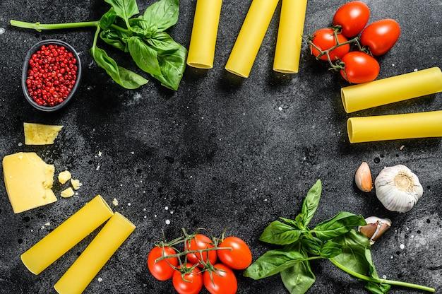Macarrão cru de canelone. cozinha italiana. ingredientes para cozinhar: manjericão, tomate cereja, parmesão, alho. fundo preto. vista do topo. copie o espaço