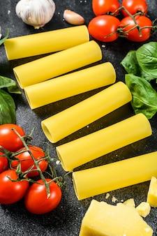 Macarrão cru de canelone. cozinha italiana. ingredientes para cozinhar: manjericão, tomate cereja, parmesão, alho. fundo preto. vista do topo