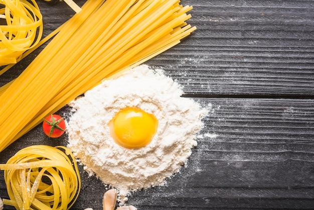 Macarrão cru de tagliatelle e espaguete com ingredientes em pano de fundo de madeira