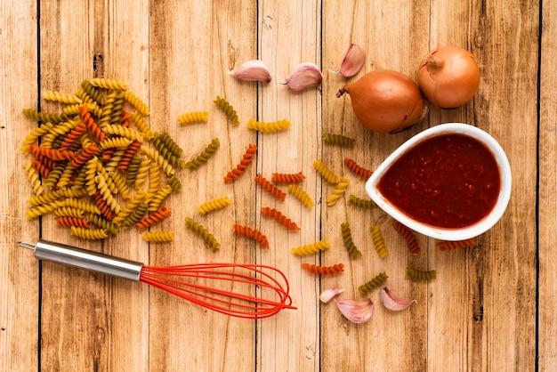 Macarrão cru e ingrediente com batedor na mesa de madeira