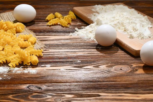 Macarrão cru e ingredientes para macarrão no fundo de madeira.