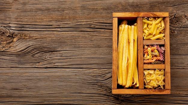 Macarrão cru em caixa de madeira com espaço de cópia