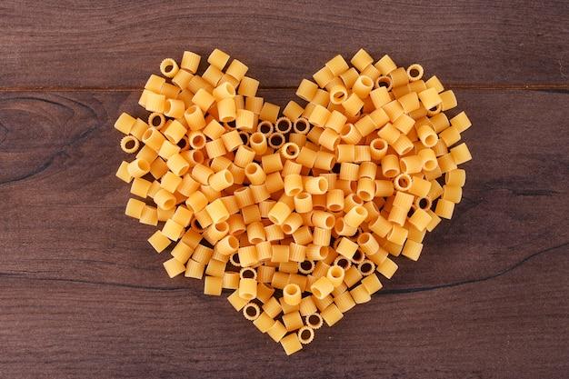 Macarrão cru em forma de coração vista superior na superfície de madeira