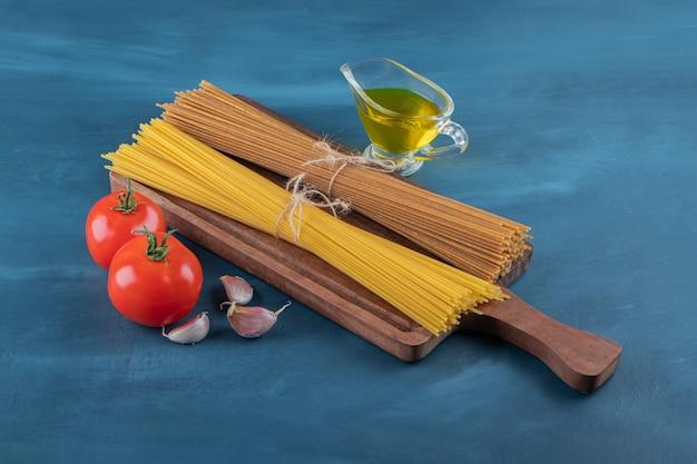 Macarrão cru em uma placa de madeira com vegetais e óleo sobre uma superfície azul escura.